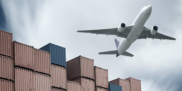 Airplane_flying_over_containers_small
